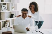 Young Pakistani Freelancer With Wife Working At Home. Husband In Glasses. Young Family Concept. Free poster
