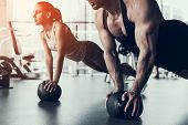 Young Man And Woman Training In Fitness Club. Man With Athletic Body. Healthy Lifestyle And Sport Co poster