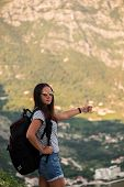 Young Backpacking Adventurous Woman Hitchhiking On The Road. Traveling Backpacks Volume, Packing Ess poster