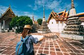 Young Woman Traveler With Backpack And Hat Looking The Map In Wat Pho At Bangkok Thailand. Traveling poster