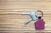 key chain with house symbol and keys on wooden background,Real estate concept poster