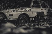Old Wrecked Car In Black And White Scene. Abandoned Rusty Car In The Forest On Bokeh Background. Dec poster
