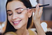 Everyday Makeup. Pleasant Smiling Makeup Artist Feeling Joyful While Finishing Her Everyday Makeup poster