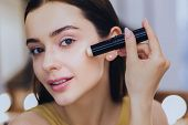 Concealer Stick. Charming Beautiful Woman Using Concealer Stick While Putting Makeup On poster