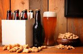 A glass of beer next to a six pack in a rustic tavern setting. Shelled peanuts in a bowl and strewn on the wood table surface. A blank picture frame hangs on the wall ready for your type or image.