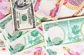 stock photo of ten thousand dollars  - pile of money in iraqi dinar and american dollars - JPG