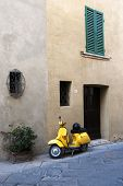 stock photo of vespa  - Yellow vespa scooter near a old house - Tuscany corner - Italy