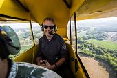 Pilot flying small aircraft with farm land in background