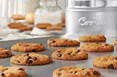 Baking still life of freshly baked chocolate chips cookies on non-stick cookie sheet with canisters,