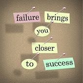 The words Failure Brings You Closer to Success on pieces of paper pinned to a bulletin board, encour