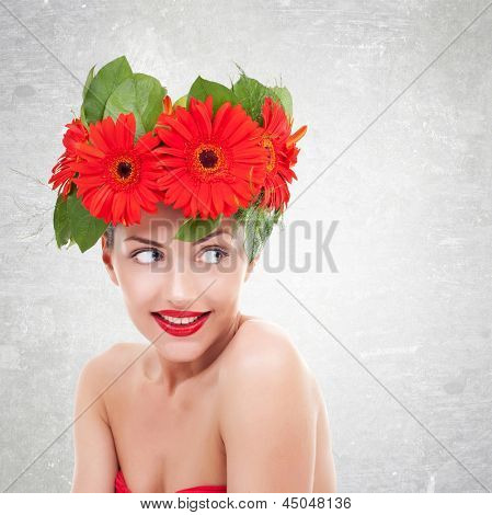 young  woman with red gerbera flowers on her head  looking to her side, on a gray background poster