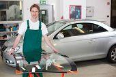 Glazier Handling Car Windshield In Garage