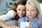 Teenager and woman listening to music with smartphone