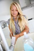 Niña en la cocina, lavar sus manos