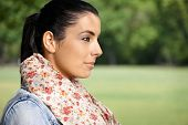 Portrait of young woman in park side view.