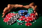 stock photo of poker hand  - Poker chips and hands above it on green table - JPG