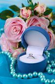 Rose en verlovingsring op blauw doek