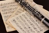 stock photo of clarinet  - Musical notes and clarinet on wooden table - JPG