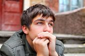stock photo of sad eyes  - sad young man portrait on the old house background - JPG