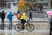 foto of bicycle gear  - Side view of young man in protective gear with backpack riding bicycle on street - JPG