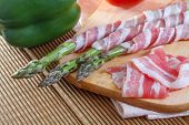 stock photo of bacon  - Bacon and asparagus on a wooden background - JPG
