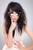 sexy young fashion woman posing with a hand on her waist and with a finger on her face while looking at the camera with an eyebrow raised behind her sunglasses. on gray background