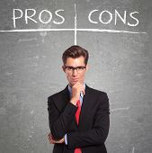 stock photo of disadvantage  - young business man in front of a pros and cons empty list - JPG