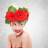 image of headings  - young  woman with red gerbera flowers on her head  looking to her side - JPG