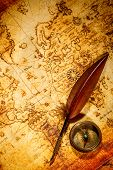 Vintage still life. Vintage compass and goose quill pen lying on an old map.