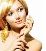Beauty Blonde Fashion Model Girl With Golden Earrings. Beautiful Hair and Nails. Manicure and Skincare concept