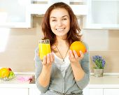 Healthy Girl with Orange Juice in the Kitchen. Diet and Healthy Eating Concept