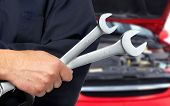 Hand with wrench. Auto mechanic in car repair .