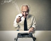 stock photo of typewriter  - senior journalist writing with a typewriter - JPG