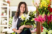 Friendly Asian florist or Saleswoman in a flower shop, holding a flower bouquet