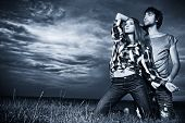 Romantic young couple in casual clothes sitting together in a field on a background of the storm sky