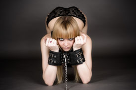 pic of debauchery  - beautiful woman in handcuffs kneeling isolated on gray - JPG