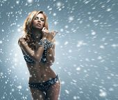 Young and beautiful girl in sexy lingerie walking through the blizzard