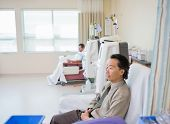 Man waiting for treatment while patient receiving renal dialysis in background at hospital room