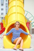 Smiling girl in striped dress sitting at bottom of yellow slide on the playground