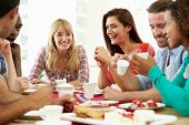 stock photo of biscuits  - Group Of Friends Having Cheese And Coffee Dinner Party - JPG