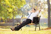 Young businessperson sitting on a wooden bench and relaxing in a park