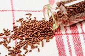 picture of jimmy  - Brown chocolate sprinkles falling from bottle on to kitchen towel - JPG