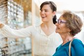 Young woman assisting senior female customer in selecting glasses at store