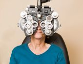 Senior woman looking through phoropter during eye exam