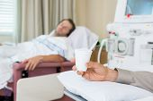 Male cancer patient's hand holding glass of crushed ice in dialysis room at hospital