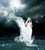 stock photo of greek  - Woman in Splashing Dress Walking on Stormy Sea - JPG