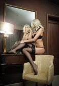 stock photo of mirror  - Beautiful blonde woman in black lingerie looking into mirror - JPG