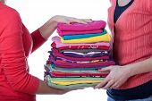 stock photo of homemaker  - Two homemakers with heap of colorful ironed washind - JPG