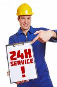 Construction worker advertising 24h service on a clipboard