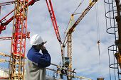 site-worker directing cranes inside large construction industry